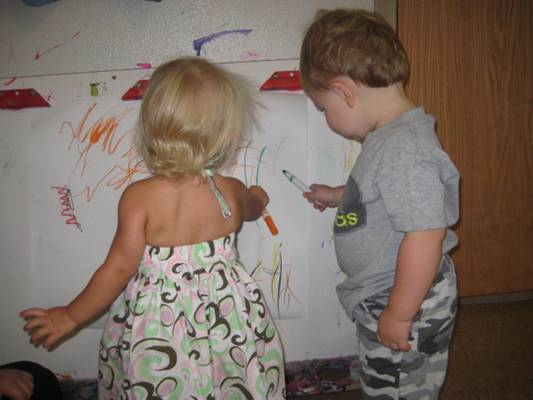 Toddler girl and boy drawing with markers
