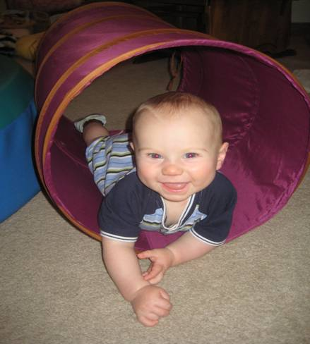 Infant smiling and laying in a tube